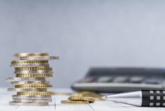 Stapel Euromünzen, Stift und Taschenrechner auf einem Tisch