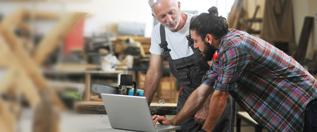 Zwei Handwerker vor Laptop