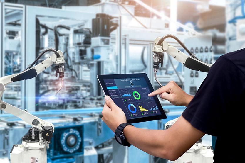 Person hält Tablet vor einer Maschine